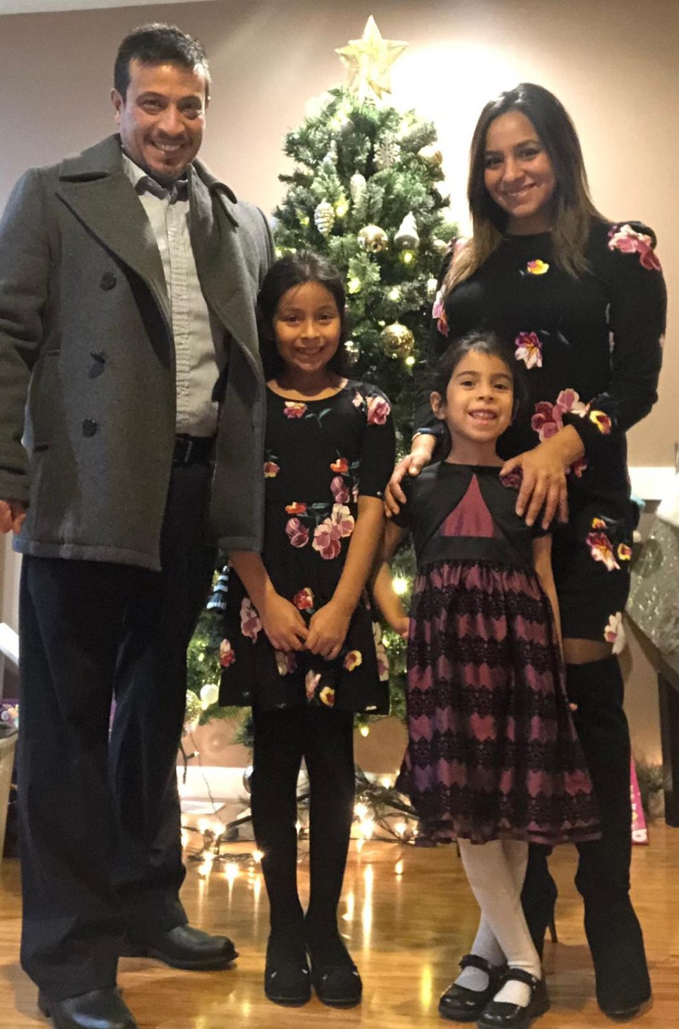 Victor Sanchez, LASM Treasurer, and his wife Heidi Sanchez, LASM Law and Culture Representative, stand with their two children in front of a Christmas tree smiling
